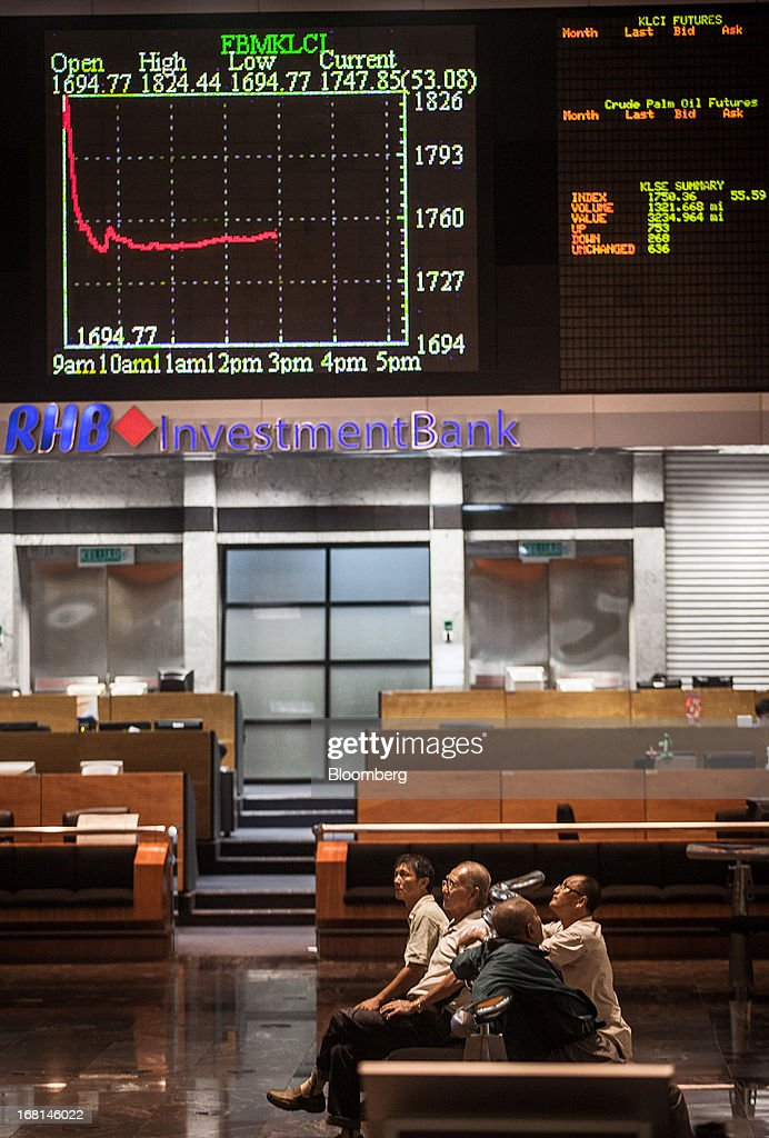 Investors sit beneath a chart displaying the Kuala Lumpur Composite Index (KLCI) as they monitor stock prices in the trading gallery at the RHB Investment Bank Bhd. headquarters in Kuala Lumpur, Malaysia, on Monday, May 6, 2013. The biggest surge in Malaysian stocks since 2008 has turned into a money-losing day for investors who piled in at the height of the rally sparked by Prime Minister Najib Razak's election victory. Photographer: Sanjit Das/Bloomberg via Getty Images
