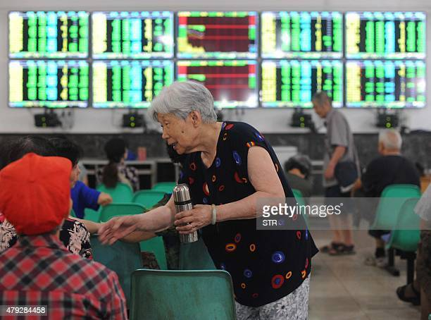 Investors talk to each other as they check stock prices at a securities firm in Wuhan in central China's Hubei province on July 3 2015 Shanghai...