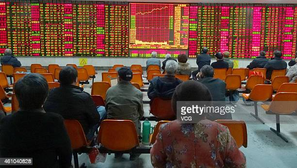 Investors watch a digital screen displaying the prices of China's stock market on January 5 2015 in Shaoxing Zhejiang province of China China's stock...