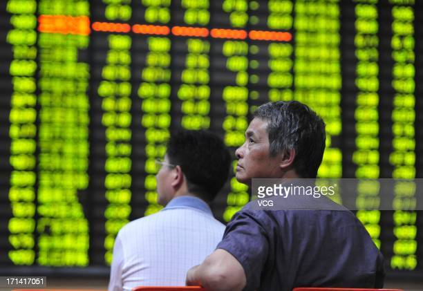 Investors watch the electronic board at a stock exchange hall on June 24 2013 in Jiujiang China Chinese shares dropped remarkably on Monday The...