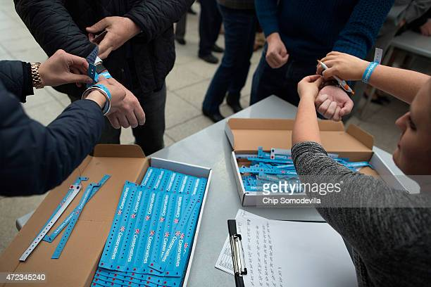 Invited guests and Conservative Party members are given wrist bands as they arrive for Prime Minister David Cameron's final campaign rally for the...