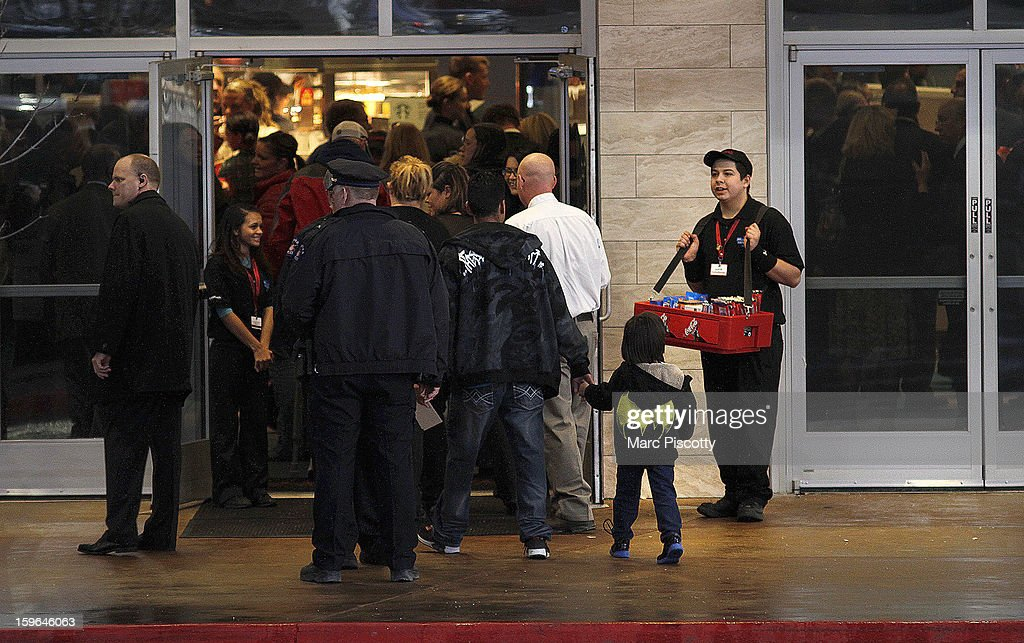 Invited guests including a little boy wearing a Batman sweatshirt make their way into a reopening ceremony and evening of remembrance at the Cinemark Century 16 Theaters on January 17, 2013 in Aurora, Colorado. The theater was the site of a mass shooting on July 20, 2012 that killed 12 people and wounded dozens of others.