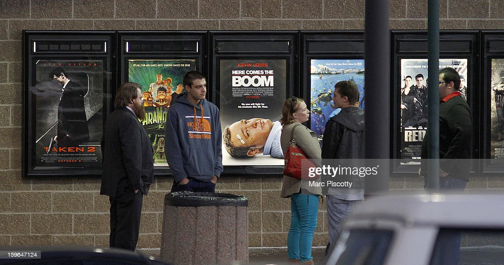 Invited guests stand by a line of movie posters before making their way into a reopening ceremony for the Cinemark Century 16 Theaters on January 17, 2013 in Aurora, Colorado. The theater was the site of a mass shooting on July 20, 2012 that killed 12 people and wounded dozens of others.