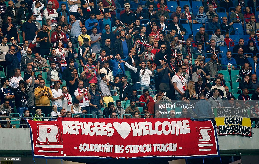 Invited refugees celebrate with fans of Leipzig during the Second Bundesliga match between RB Leipzig and SC Paderborn at Red Bull Arena on September...
