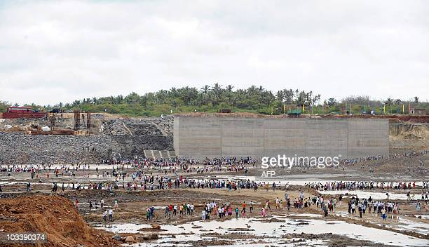 Invitees and workers walk at the basin of an under construction port at Hambantota on August 15 as it is being filled with sea water Sri Lankan...