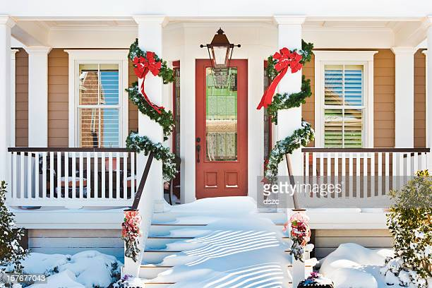 inviting Christmas front doorway with snow on porch stairs