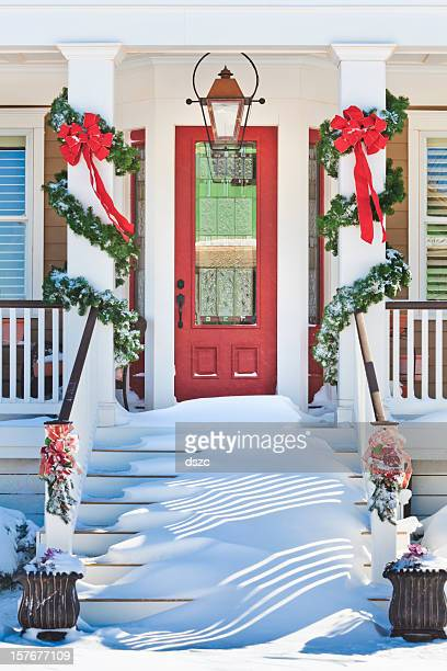 inviting front doorway with snowy Chrismas porch
