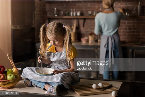 Involved girl mixing eggs sitting on the table : Stock Photo