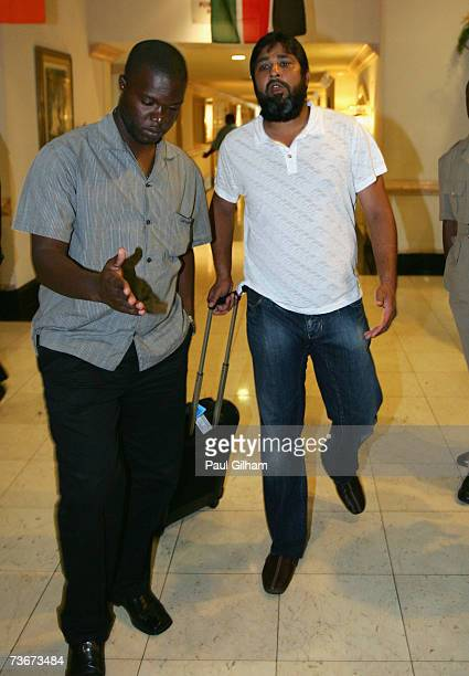 Inzamam UlHaq of Pakistan is led by security with his bags shortly before leaving the team hotel to catch a flight out of Kingston on March 22 2007...
