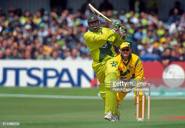InzamamulHaq of Pakistan drives watched by Adam Gilchrist of Australia during the ICC World Cup match between Australia and Pakistan at Headingley in...