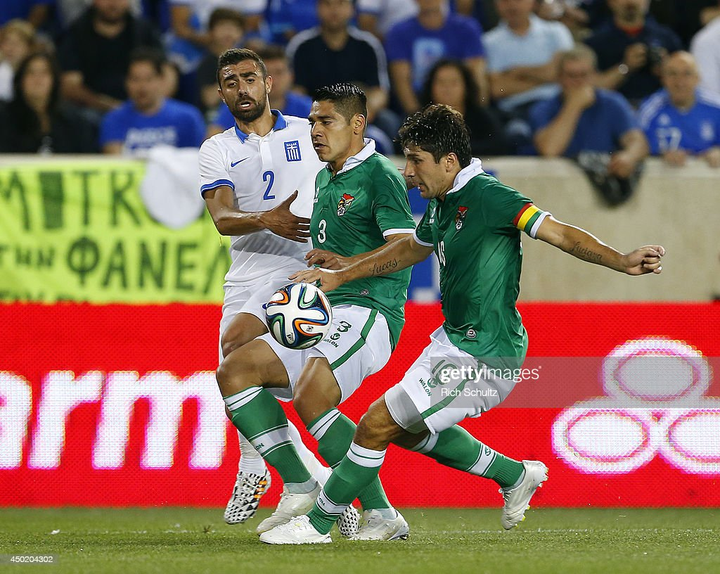Ioannis Maniatis #2 of Greece kicks the ball between Luis Alberto Gutierrez #3 and <a gi-track='captionPersonalityLinkClicked' href=/galleries/search?phrase=Ronald+Raldes&family=editorial&specificpeople=771201 ng-click='$event.stopPropagation()'>Ronald Raldes</a> #16 of Bolivia during the second half of an international friendly match at Red Bull Arena on June 6, 2014 in Harrison, New Jersey. Greece defeated Bolivia 2-1.