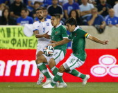 Ioannis Maniatis of Greece kicks the ball between Luis Alberto Gutierrez and Ronald Raldes of Bolivia during the second half of an international...