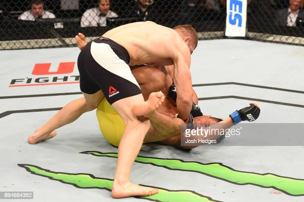 Ion Cutelaba of Moldova punches Henrique da Silva of Brazil in their light heavyweight fight during the UFC Fight Night event at the Spark Arena on...