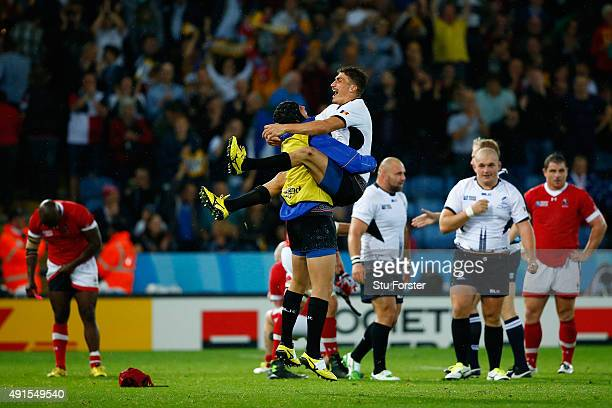 Ionut Botezatu of Romania jumps into the arms of a team mate in celebration after the 2015 Rugby World Cup Pool D match between Canada and Romania at...