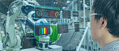 iot industry 4.0 concept,industrial engineer(blurred) using smart glasses with augmented mixed with virtual reality technology to monitoring machine in real time.Smart factory use Automation robot arm