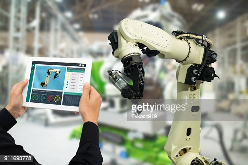 iot industry 4.0 concept,industrial engineer using software (augmented, virtual reality) in tablet to monitoring machine in real time.Smart factory use Automation robot arm in automotive manufacturing : Foto stock