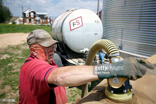 Iowa farmer Ernie 'George' Goebel loads fertilizer into the tanks on a planter mounted behind his John Deere tractor on May 9 2007 near Luxemburg...