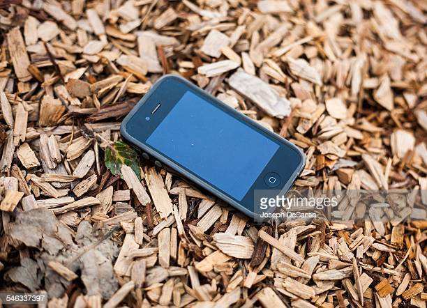 iPhone 4 in a case on wood chips