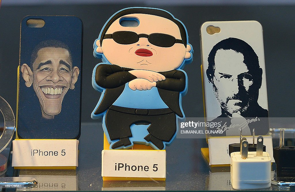 Iphone 5 covers featuring South Korean singer PSY (C), US President Barack Obama and Apple co-founder Steve Jobs are on display in New York, January 8, 2013.