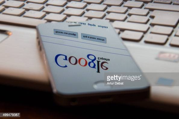iPhone 5s smartphone screen reflection of the the internet laptop browser with Google main page Internet addiction