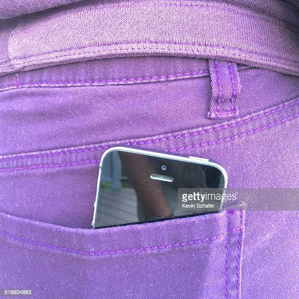 iPhone in back pocket of purple jeans
