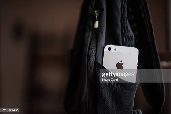 iPhone sticking out of side pocket of backpack