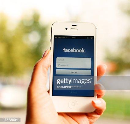iPhone メインスクリーンで Facebook の女性の手