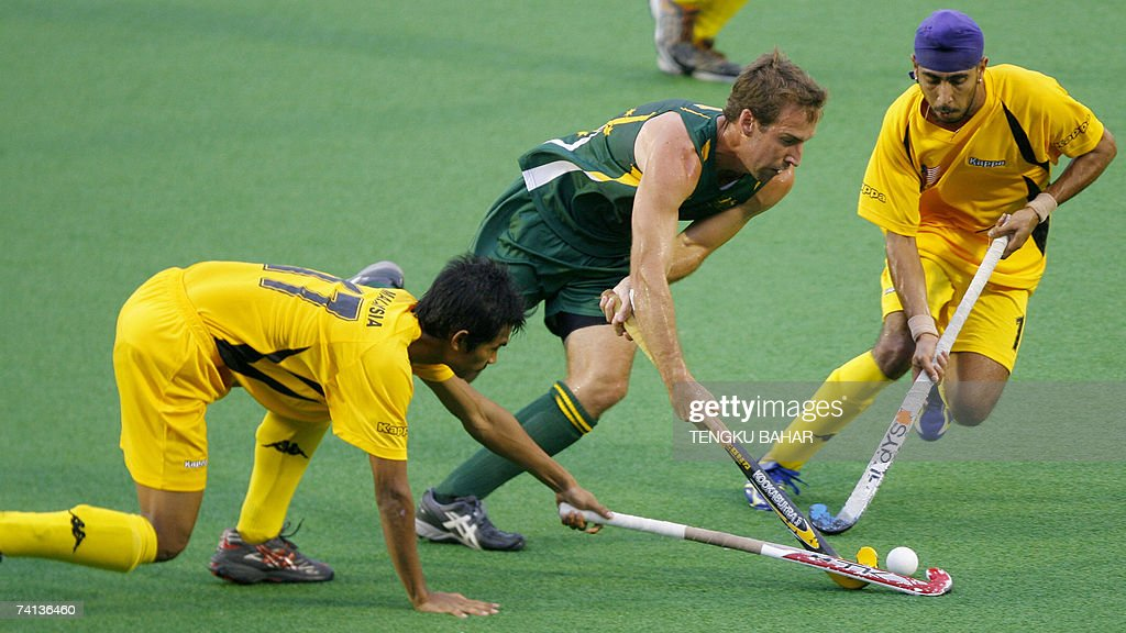 Australia's Liam DeYoung holds on to the ball while flanked by Malaysia's Kelvinder Singh and Muhammad Razie during the 16th Sultan Azlan Shah hockey...