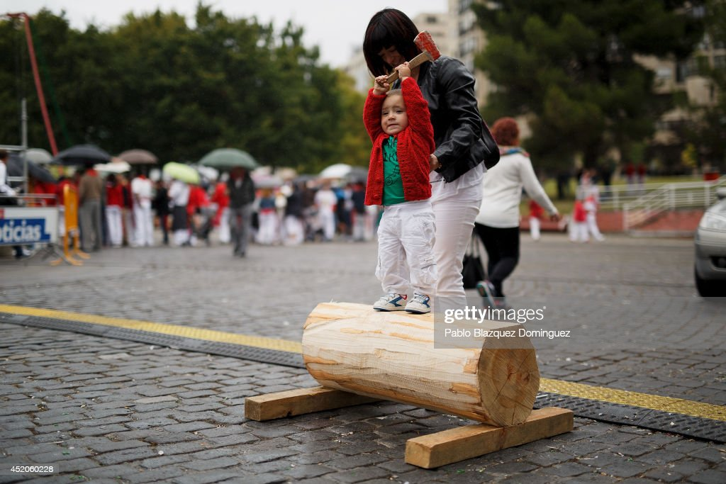 Irai Vicente, one-year old, plays with a wooden axe as he waits for his uncle to compete in a rural Basque sports contest during the seventh day of the San Fermin Running Of The Bulls festival on July 12, 2014 in Pamplona, Spain. The annual Fiesta de San Fermin, made famous by the 1926 novel of US writer Ernest Hemingway 'The Sun Also Rises', involves the running of the bulls through the historic heart of Pamplona.