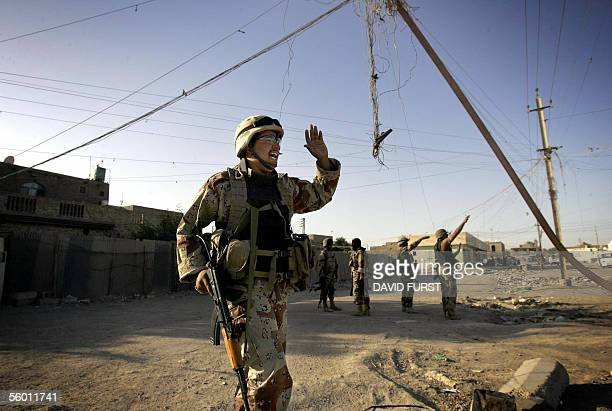 An Iraqi commando accompanied by US army soldiers from the 222 Infantry 10th Mountain Division MiTT team screams towards Iraqi civilians to avoid an...
