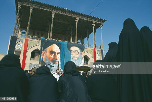 Iran Esfahan Banners of Ayatollah Khomeini and Ali Khamenei to commemorate death of Emam Husain with outlines of women in black in the foreground...