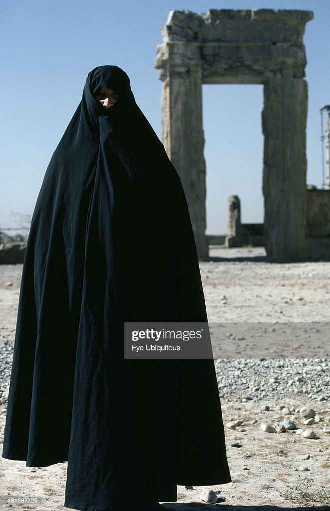 Iran Fars Province Persepolis Full length standing portrait of a woman wearing a black Chador at Persepolis