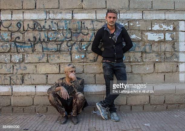 Iran Kurdistan Province Bijar iranian shiite muslim men covered in mud resting against a wall after ashura ceremony