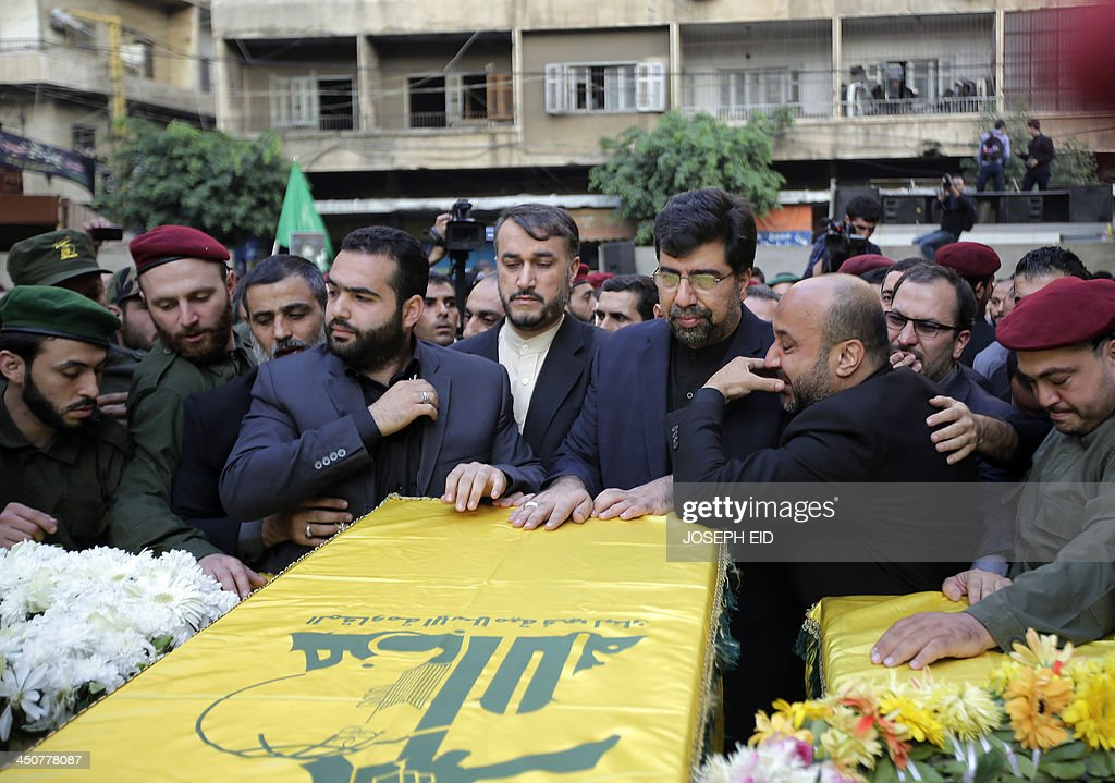 Iranian Ambassador to Lebanon Ghadanfar Rukn Abadi (C-R) and Iranian Deputy Foreign Minister Hossein Amir Abdollahian (C) touch the coffin of one of the Iranian embassy security guards, draped in the Hezbollah movement's yellow and green flag, who died in the twin suicide attack outside the Iranian Embassy in Beirut the previous day, during the funeral of the four guards in Shiah, a southern suburb of the Lebanese capital on November 20, 2013. Thousands of people turned out for a funeral for the four Iranian embassy security guards, all of whom were members of Lebanon's powerful Shiite movement Hezbollah, which is also backed by Iran and is fighting alongside Assad's troops against Sunni-led rebels.