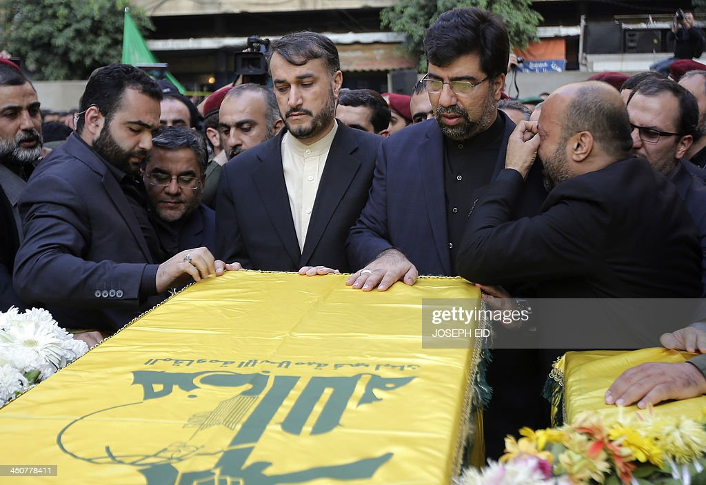 Iranian Ambassador to Lebanon Ghadanfar Rukn Abadi (C-R) and Iranian Deputy Foreign Minister Hossein Amir Abdollahian (C-L) touch the coffin of one of the Iranian embassy security guards, draped in the Hezbollah movement's yellow and green flag, who died in the twin suicide attack outside the Iranian Embassy in Beirut the previous day, during the funeral of the four guards in Shiah, a southern suburb of the Lebanese capital on November 20, 2013. Thousands of people turned out for a funeral for the four Iranian embassy security guards, all of whom were members of Lebanon's powerful Shiite movement Hezbollah, which is also backed by Iran and is fighting alongside Assad's troops against Sunni-led rebels.