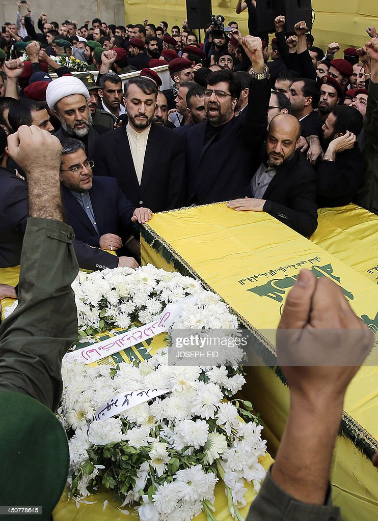 Iranian Ambassador to Lebanon Ghadanfar Rukn Abadi (C-R) and Iranian Deputy Foreign Minister Hossein Amir Abdollahian (C-L) stand next to the coffins of the Iranian embassy security guards, draped in the Hezbollah movement's yellow and green flag, who died in the twin suicide attack outside the Iranian Embassy in Beirut the previous day, during their funeral in Shiah, a southern suburb of the Lebanese capital on November 20, 2013. Thousands of people turned out for a funeral for the four Iranian embassy security guards, all of whom were members of Lebanon's powerful Shiite movement Hezbollah, which is also backed by Iran and is fighting alongside Assad's troops against Sunni-led rebels. AFP PHOTO/JOSEPH EID
