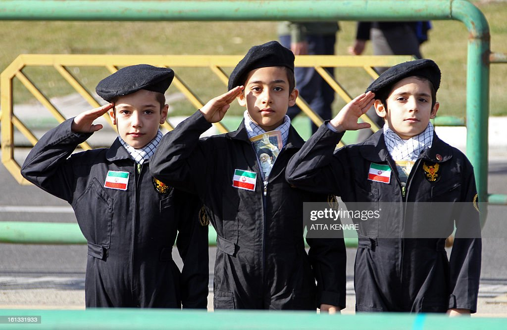 Iranian boy scouts salute during a rally in Tehran's Azadi Square (Freedom Square) to mark the 34th anniversary of the Islamic revolution on February 10, 2013. Hundreds of thousands of people marched in Tehran and other cities chanting 'Death to America' and 'Death to Israel' as Iran celebrated the anniversary of the ousting of the US-backed shah. AFP PHOTO / ATTA KENARE
