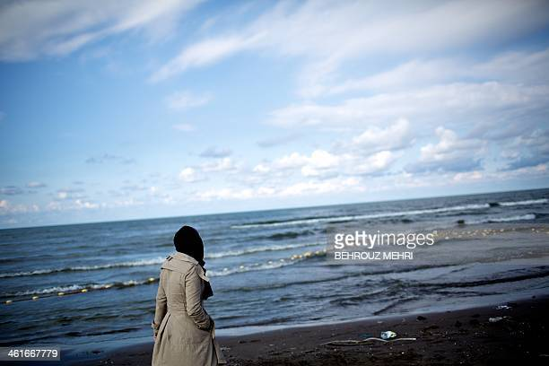 Iranian breast cancer patient Farvah walks off the coast of Caspian Sea near the northern port city of Bandar Anzali on November 1 during a trip to...