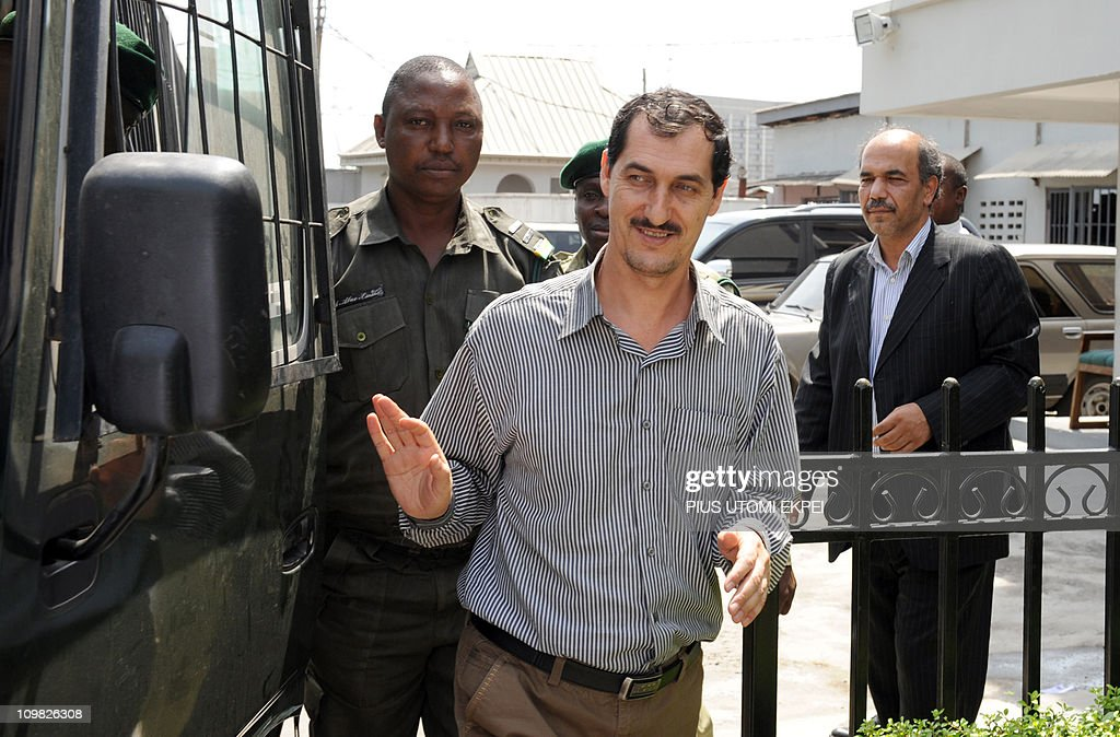 Iranian businessman and alleged Iranian Revolutionary Guard member Azim Aghajani (C) is led on March 7, 2011 to a bus taking him to prison as the consul ceneral of the Iranian Embassy, Ahmad Fakouryan (R), watches him after a hearing at the Federal High Court in Lagos. Nigerian prosecutors on March 7 amended the charges against Aghajani on trial over a shipment of rockets, explosives and grenades seized in the West African nation. The new charges are similar to the old accusations, but provide more specifics on the types of weapons involved in the October 2010 seizure, naming bombs, grenades and rockets. They accuse the two suspects of illegally importing them and say the weapons were under their control. They are also accused of having falsely declared the 13 containers seized at a Lagos port as building materials. Both men pleaded not guilty to the new charges.