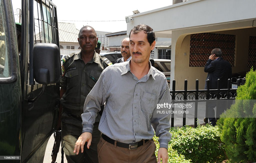 Iranian businessman and alleged Iranian Revolutionary Guard member Azim Aghajani (R) is led on March 7, 2011 to a bus taking him to prison as the consul general of the Iranian Embassy, Ahmad Fakouryan (C), watches him after a hearing at the Federal High Court in Lagos. Nigerian prosecutors on March 7 amended the charges against Aghajani on trial over a shipment of rockets, explosives and grenades seized in the West African nation. The new charges are similar to the old accusations, but provide more specifics on the types of weapons involved in the October 2010 seizure, naming bombs, grenades and rockets. They accuse the two suspects of illegally importing them and say the weapons were under their control. They are also accused of having falsely declared the 13 containers seized at a Lagos port as building materials. Both men pleaded not guilty to the new charges. AFP PHOTO / PIUS UTOMI EKPEI