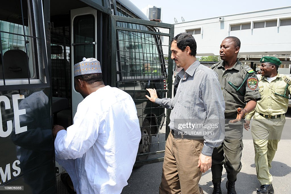 Iranian businessman and alleged Iranian Revolutionary Guard member Azim Aghajani (2nd R) and Nigerian suspect Ali Abbas Jega (L) are led on March 7, 2011 to a bus taking them to prison after a hearing at the Federal High Court in Lagos. Nigerian prosecutors on March 7 amended the charges against Aghajani and Jega on trial over a shipment of rockets, explosives and grenades seized in the West African nation. The new charges are similar to the old accusations, but provide more specifics on the types of weapons involved in the October 2010 seizure, naming bombs, grenades and rockets. They accuse the two suspects of illegally importing them and say the weapons were under their control. They are also accused of having falsely declared the 13 containers seized at a Lagos port as building materials. Both men pleaded not guilty to the new charges.