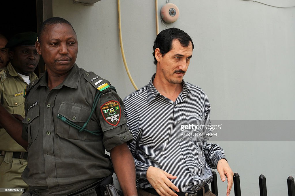 Iranian businessman and alleged Iranian Revolutionary Guard member Azim Aghajani (R) is led on March 7, 2011 to a bus taking him to prison after a hearing at the Federal High Court in Lagos. Nigerian prosecutors on March 7 amended the charges against Aghajani and Nigerian suspect Ali Abbas Jega on trial over a shipment of rockets, explosives and grenades seized in the West African nation. The new charges are similar to the old accusations, but provide more specifics on the types of weapons involved in the October 2010 seizure, naming bombs, grenades and rockets. They accuse the two suspects of illegally importing them and say the weapons were under their control. They are also accused of having falsely declared the 13 containers seized at a Lagos port as building materials. Both men pleaded not guilty to the new charges. AFP PHOTO / PIUS UTOMI EKPEI