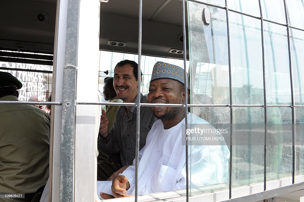 Iranian businessman and alleged Iranian Revolutionary Guard member Azim Aghajani (L) and Nigerian suspect Ali Abbas Jega (R) smile on March 7, 2011 in a bus taking him to prison after a hearing at the Federal High Court in Lagos. Nigerian prosecutors on March 7 amended the charges against Aghajani and Jega on trial over a shipment of rockets, explosives and grenades seized in the West African nation. The new charges are similar to the old accusations, but provide more specifics on the types of weapons involved in the October 2010 seizure, naming bombs, grenades and rockets. They accuse the two suspects of illegally importing them and say the weapons were under their control. They are also accused of having falsely declared the 13 containers seized at a Lagos port as building materials. Both men pleaded not guilty to the new charges.