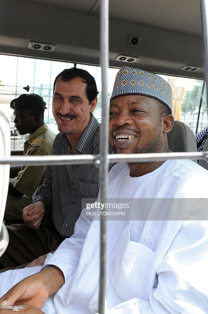 Iranian businessman and alleged Iranian Revolutionary Guard member Azim Aghajani (C) and Nigerian suspect Ali Abbas Jega (R) smile on March 7, 2011 in a bus taking him to prison after a hearing at the Federal High Court in Lagos. Nigerian prosecutors on March 7 amended the charges against Aghajani and Jega on trial over a shipment of rockets, explosives and grenades seized in the West African nation. The new charges are similar to the old accusations, but provide more specifics on the types of weapons involved in the October 2010 seizure, naming bombs, grenades and rockets. They accuse the two suspects of illegally importing them and say the weapons were under their control. They are also accused of having falsely declared the 13 containers seized at a Lagos port as building materials. Both men pleaded not guilty to the new charges.