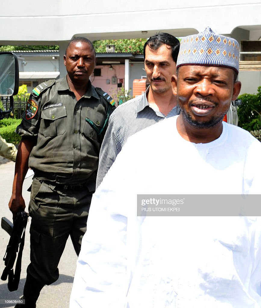 Iranian businessman and alleged Iranian Revolutionary Guard member Azim Aghajani (C) and Nigerian suspect Ali Abbas Jega (R) are led on March 7, 2011 to a bus taking them to prison after a hearing at the Federal High Court in Lagos. Nigerian prosecutors on March 7 amended the charges against Aghajani and Jega on trial over a shipment of rockets, explosives and grenades seized in the West African nation. The new charges are similar to the old accusations, but provide more specifics on the types of weapons involved in the October 2010 seizure, naming bombs, grenades and rockets. They accuse the two suspects of illegally importing them and say the weapons were under their control. They are also accused of having falsely declared the 13 containers seized at a Lagos port as building materials. Both men pleaded not guilty to the new charges.