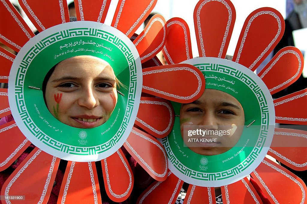 Iranian children bearing headdresses in the colours of their national flag attend a rally in Tehran's Azadi Square (Freedom Square) to mark the 34th anniversary of the Islamic revolution on February 10, 2013. Hundreds of thousands of people marched in Tehran and other cities chanting 'Death to America' and 'Death to Israel' as Iran celebrated the anniversary of the ousting of the US-backed shah. AFP PHOTO / ATTA KENARE