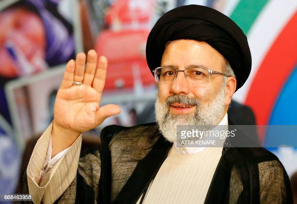 Iranian cleric and head of the Imam Reza charitable foundation Ebrahim Raisi gestures after registering his candidacy for the upcoming presidential...