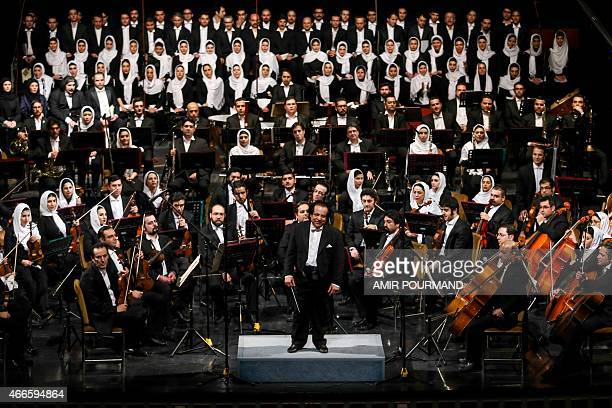 Iranian conductor Ali Rahbari and the Tehran Symphony Orchestra are greeted by the audience after performing at the Vahdat Hall in Tehran on March 16...