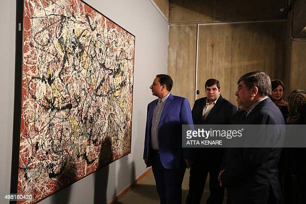 Iranian Culture Minister Ali Jannati looks at US artist Jackson Pollock's 'Mural on Indian Red Ground' during the opening ceremony of an exhibition...