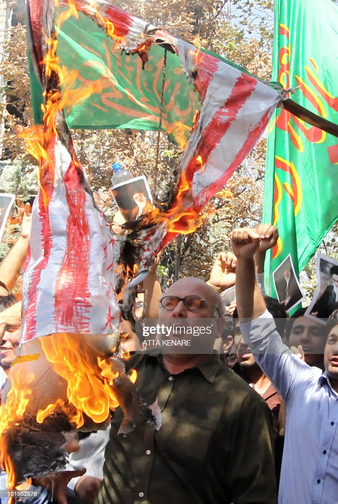 Iranian demonstrators burn the US flag during a protest against a film mocking Islam, on September 13, 2012 near the Swiss embassy in Tehran . Up to 500 people protested in Tehran over the anti-Islam film made in the United States, chanting 'Death to America!' and death to the movie's director. The rally, near the Swiss embassy that handles US interests in the absence of US-Iran diplomatic ties, ended peacefully two hours later.